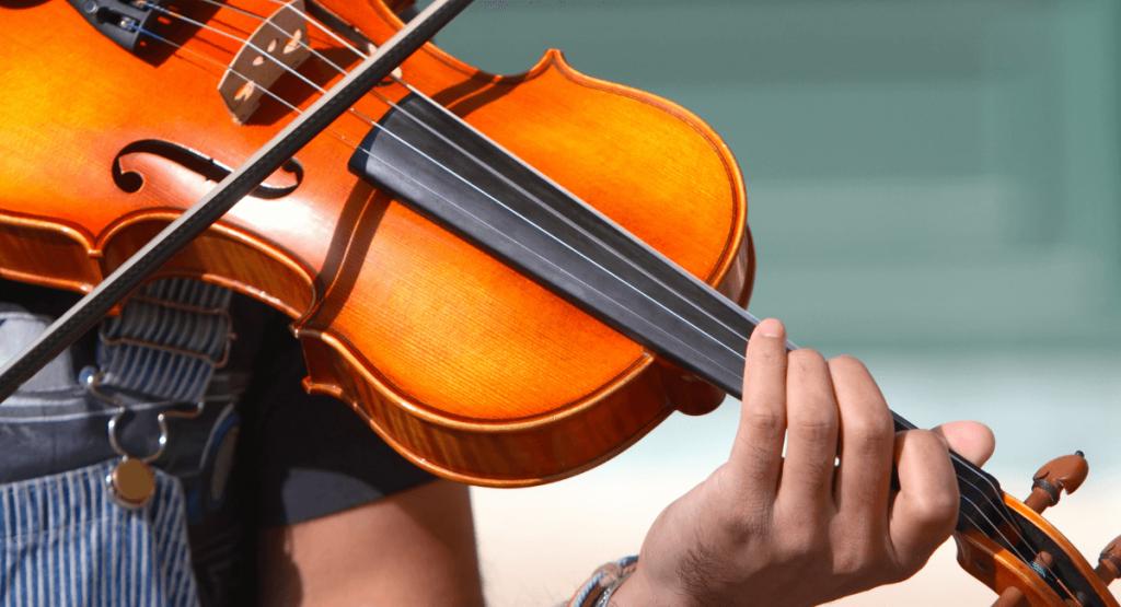 Person playing violin as beginner violin player